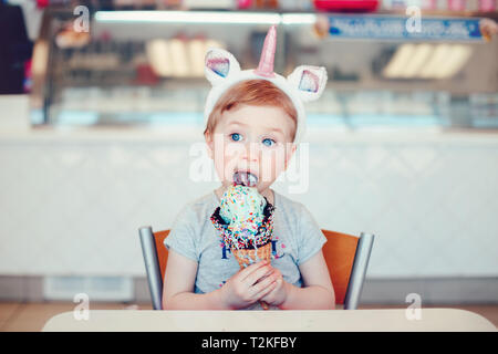Cute adorable funny Caucasian blonde girl child with blue eyes wearing unicorn headband eating licking ice cream in large waffle cone with sprinkles.