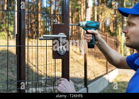 worker installing the lock for new metal fence gates - Stock Photo