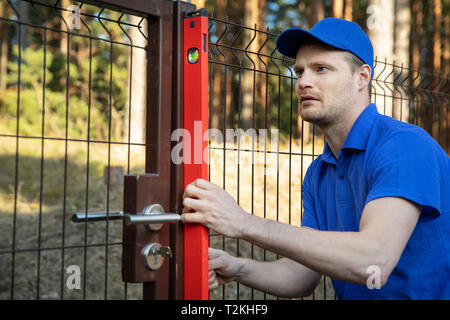 fence construction - worker check the level of metal post - Stock Photo