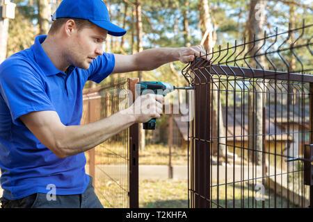 property territory fencing - man screws metal fence panel - Stock Photo