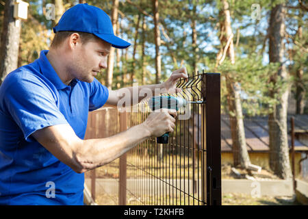 fencing services - worker installing welded metal mesh fence - Stock Photo