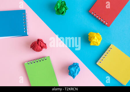Flat lay of multicolored notepads and crushed paper abstract. - Stock Photo