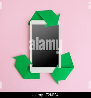 Electronic device tablet or mobile phone and recycle symbol on pastel pink background minimal eco creative concept. - Stock Photo
