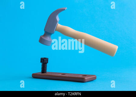 A hammer nail hit into a wooden plank minimal creative construction concept. - Stock Photo
