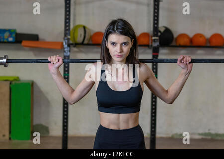 The girl is engaged with a barbell in the gym - Stock Photo