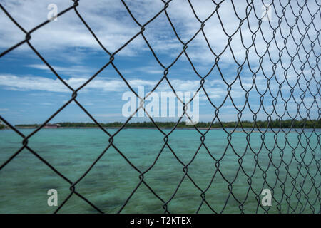 A Close up of fence with blurry turquoise water on the background taken at Harapan Island, Indonesia - Stock Photo