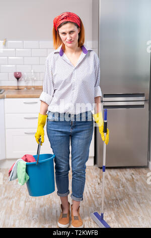 image of tired and angry housewife in protective gloves holding a flat wet-mop and bucket with rags while cleaning her house. spring cleaning - Stock Photo