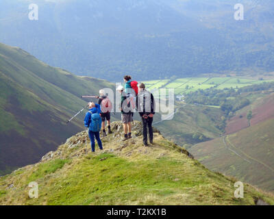 A Fellwalking Group Standing and Looking from Knott Ridge on the Wainwright  Ard Crags, Newlands Valley, Lake District National Park, Cumbria, UK. - Stock Photo