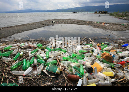 plastic trash and bottles on the edge of the lake - Stock Photo