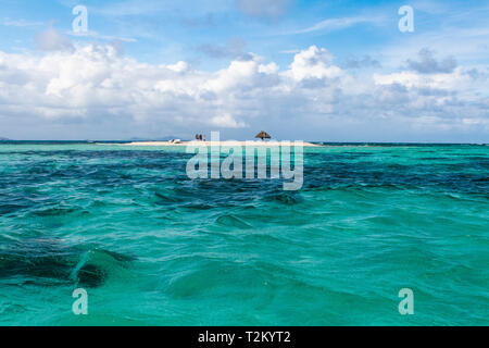 Mopian Island View from the Sea: With Small Group of Visitors, Dinghy and Solitary Parasol on this Tiny Island. Image Illustrates Size and Structure. - Stock Photo