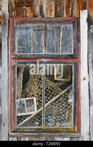 The window of the old ruined village house in which the fisherman once lived. Fishing nets behind glass - Stock Photo