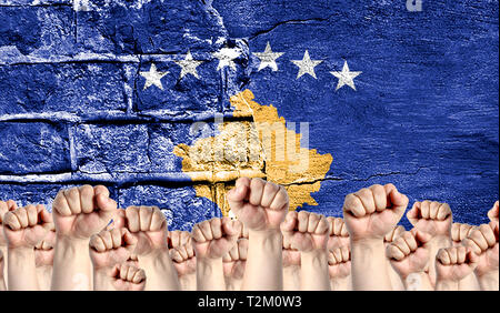 Male hands clenched in a fist raised up against the backdrop of a destroyed brick wall with a flag of Kosovo. The concept of the labor movement from t - Stock Photo
