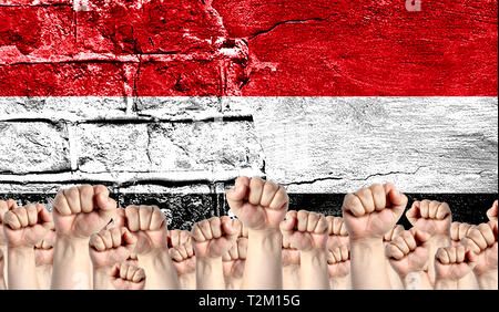Male hands clenched in a fist raised up against the backdrop of a destroyed brick wall with a flag of Yemen. The concept of the labor movement from th - Stock Photo