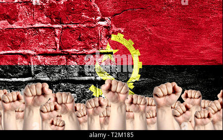 Male hands clenched in a fist raised up against the backdrop of a destroyed brick wall with a flag of Angola. The concept of the labor movement from t - Stock Photo