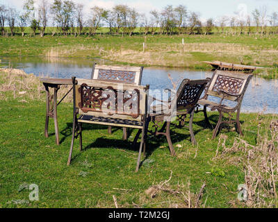 Heavy cast iron and wood garden furniture in a slightly surreal location in the middle of an area of meadow and man-made ponds. - Stock Photo