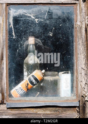 A glimpse through the window of an old garden shed with abandoned bottles and cans seen through cobweb covered glass. - Stock Photo