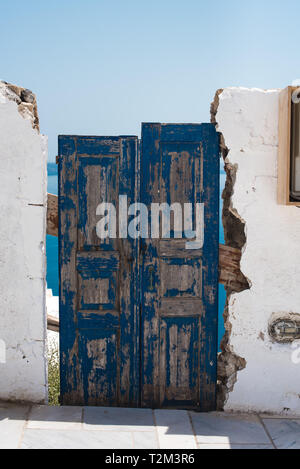 An old, worn out door blocks a passageway in Santorini, Greece. - Stock Photo