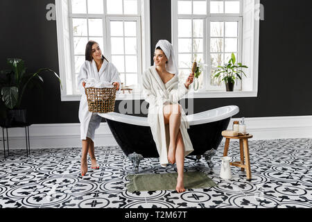 Cute young two women dressed in white dressing gowns and towels on the head have fun in the bathroom. Leisure - Stock Photo