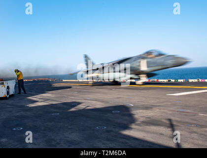190401-N-UP035-0238  U.S. 5TH FLEET AREA OF OPERATIONS (April 1, 2019) An AV-8B Harrier launches from the flight deck of the Wasp-class amphibious assault ship USS Kearsarge (LHD 3). Kearsarge is the flagship for the Kearsarge Amphibious Ready Group and, with the embarked 22nd Marine Expeditionary Unit, is deployed to the U.S. 5th Fleet area of operations in support of naval operations to ensure maritime stability and security in the Central region, connecting the Mediterranean and the Pacific through the western Indian Ocean and three strategic choke points. (U.S. Navy photo by Mass Communica - Stock Photo