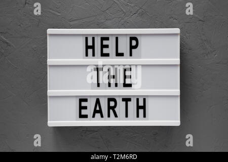 'Help the Earth' words on lightbox over concrete background, top view. Flat lay, overhead, from above. - Stock Photo