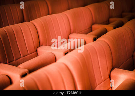 A row of red armchairs in a cinema or theater hall - Stock Photo