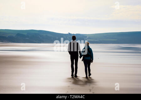 A couple holding hands walking together on a quiet sandy beach at low tide. Woolacombe, North Devon, England, UK, Britain - Stock Photo