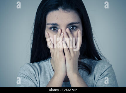 Close up portrait of a young sad woman, serious and concerned, looking worried and thoughtful suffering from migraines. Isolated on neutral background - Stock Photo