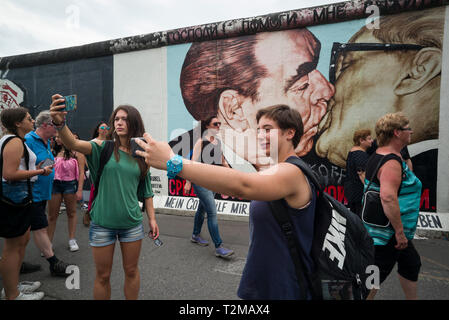 Berlin. Germany. Tourists pose for photos infront of one of the remaining sections of the Berlin Wall at the East Side Gallery.   Tourists pose for ph - Stock Photo