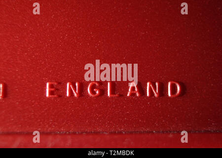 Made in England inscription printed on red plastic surface, close-up - Stock Photo