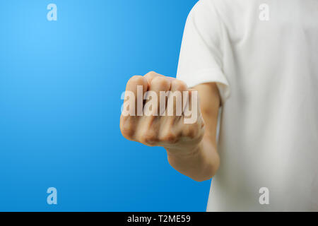 A white shirt man showing fist with his hand front view on blue background. Carefully cut out by pen tool and insert clipping path. - Stock Photo