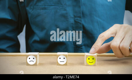 Conceptual the customer responded to the survey. The client using hand choose happy face smile icon on wood block. Depicts that customer is very satis - Stock Photo