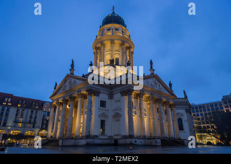 Lit Neue Kirche (Deutscher Dom, German Church or German Cathedral) in Berlin, Germany, at the Gendarmenmarkt Square in Berlin, Germany, in the evening - Stock Photo