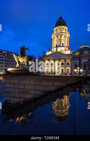 Lit Neue Kirche (Deutscher Dom, German Church or German Cathedral) and a statue in front of the Konzerthaus Berlin at Gendarmenmarkt Square at dusk. - Stock Photo