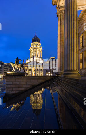 Lit Neue Kirche (Deutscher Dom, German Church or German Cathedral) and front of the Konzerthaus Berlin at the Gendarmenmarkt Square in Berlin at dusk. - Stock Photo