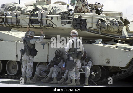 30th October 1993 U.S. Army soldiers shelter from the fierce heat in the shade of their M1A1 Abrams tank of the 24th Infantry Division, 1st Battalion of the 64th Armored Regiment. They have just arrived in the new port in Mogadishu, Somalia. - Stock Photo