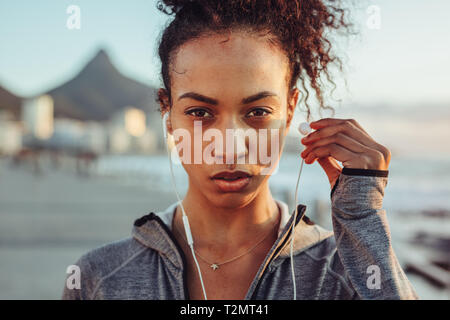 Close up of woman athlete wearing earphones outdoors. Female listening to music during workout. - Stock Photo