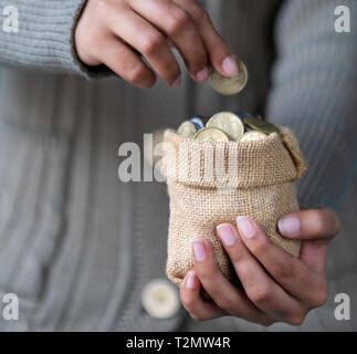 Saving money or coins in a sack holding in a young female hand for brighter future education. - Stock Photo