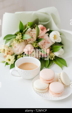 Elegant sweet dessert macarons, cup of coffee and pastel colored beige flowers bouquet on white table closeup - Stock Photo