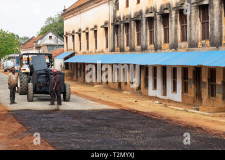 Kanadukathan, India - March 12, 2018: Road workers spraying liquid tar onto hardcore as part of highway resurfacing in rural Tamil Nadu state - Stock Photo