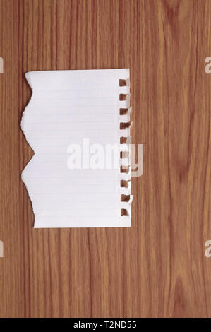 Sheet of notebook paper with torn edge blank ripped piece on isolated over wooden table background. Empty Damaged Rip Paper Shape. Clipping path, copy - Stock Photo