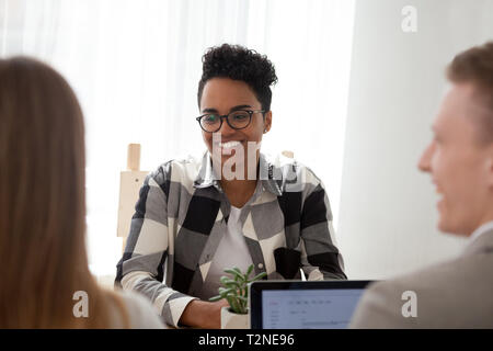 Happy black woman team leader with colleagues workers sitting together in office boardroom. Successful American female passing job interview, advisors - Stock Photo