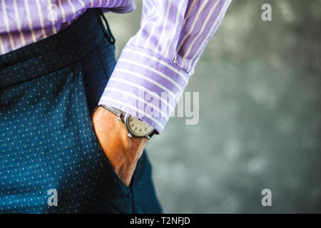 Close-up of Male Hand in Pants Pocket with Elegant Wristwatch. Caucasian Businessman in Striped Shirt Wearing Stylish Dress Watch. Fashion and Punctua - Stock Photo