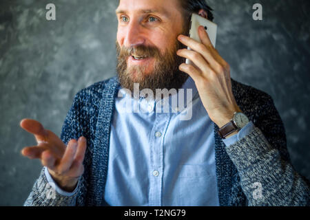 Happy Smiling Bearded Man Talk at Phone and Gesticulates During Conversation. Open and Friendly Communication with a Pleasant Interlocutor. Good News  - Stock Photo