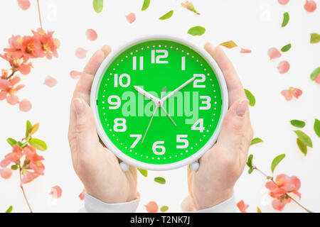 Female hands holding vintage alarm clock flat lay with colorful springtime floral decoration of petals and leaves - Stock Photo