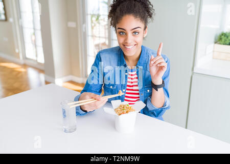 Young african american woman eating asian noodles from delivery box surprised with an idea or question pointing finger with happy face, number one - Stock Photo