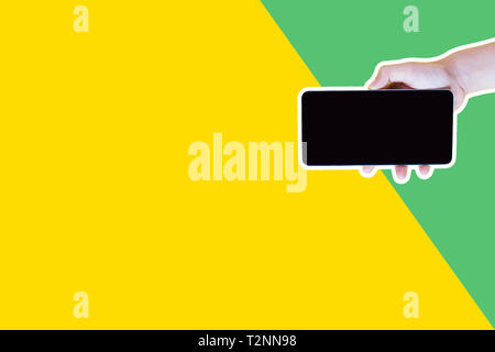 Collage in magazine style and pop art style. Hand holding smartphone over yellow and green background. - Stock Photo