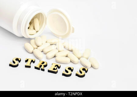 White oval pills spilled out of a white bottle on a white background labeled stress. The concept of the use of drugs for normal functioning. - Stock Photo