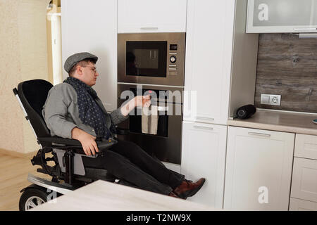Physically impaired man switching on oven in kitchen - Stock Photo