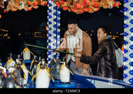 Couple trying to hook a penguin on a fairground stall - Stock Photo