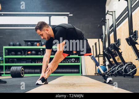 Man with prosthetic leg stretching in gym - Stock Photo